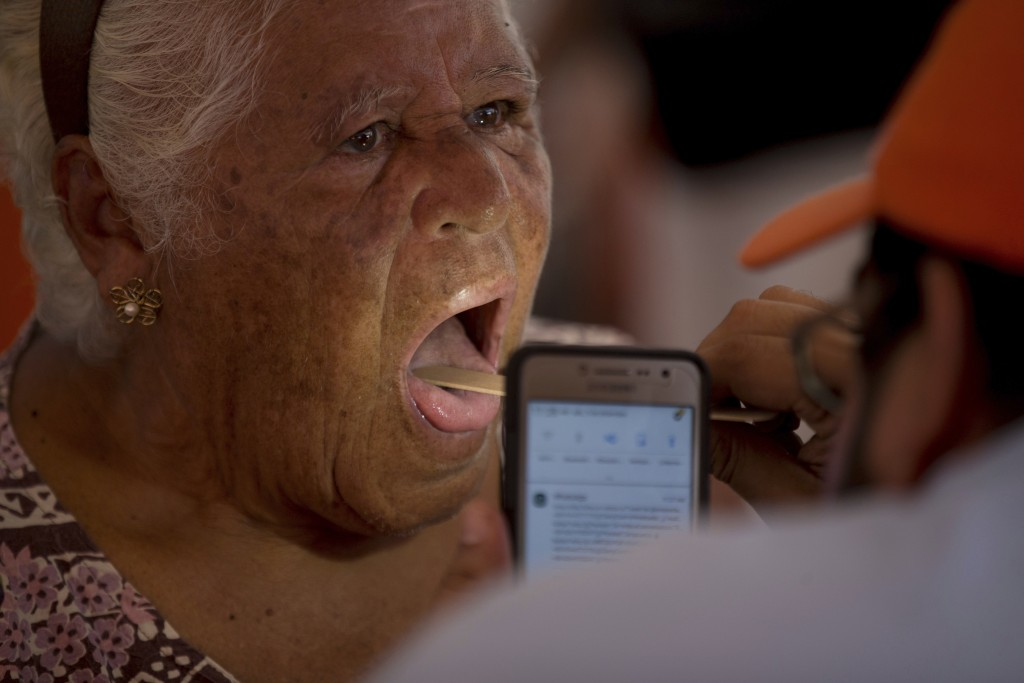 In this Dec. 9, 2017 photo, an elderly woman has her mouth inspected by Dr. Winston Flores, who uses the lamp of his smart phone during a free medical...