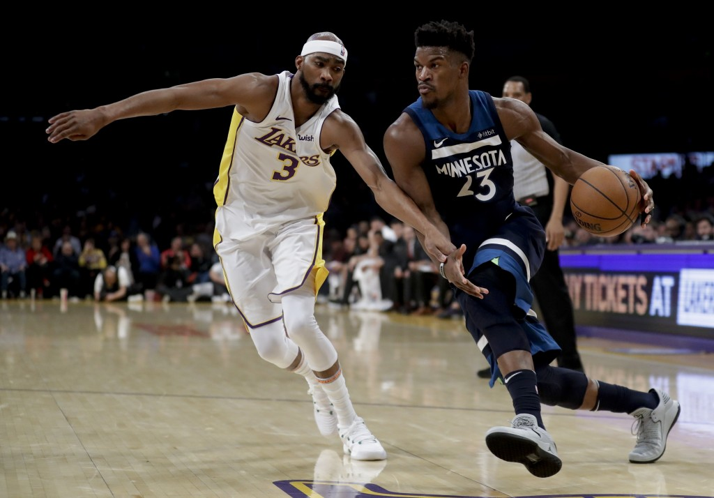 Minnesota Timberwolves guard Jimmy Butler drives to the basket past Los Angeles Lakers forward Corey Brewer during the first half of an NBA basketball...