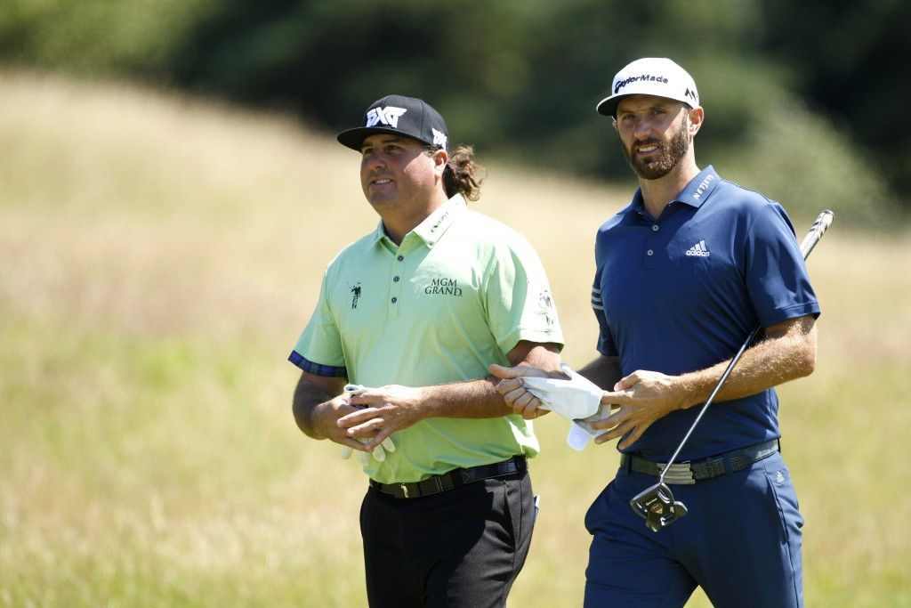 FILE - This July 17, 2017 file photo shows Pat Perez, left, and Dustin Johnson of the U.S. on the 5th hole during the second practice day at the Briti...