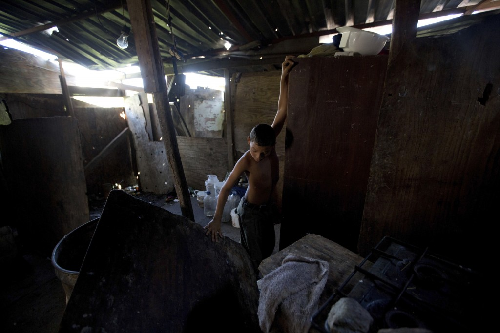 In this Dec. 9, 2017 photo, David Martinez plays inside his home, located in a neighborhood where the opposition set up a free food and medical campai...