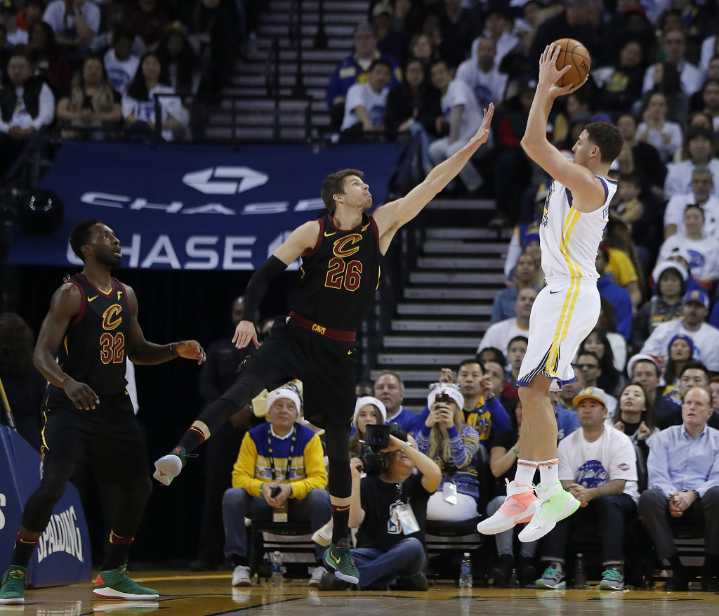Golden State Warriors guard Klay Thompson (11) shoots over Cleveland Cavaliers guard Kyle Korver (26) during the first half of an NBA basketball game ...