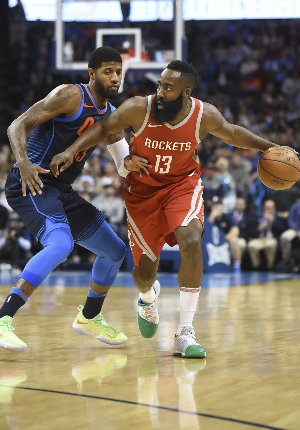Houston Rockets' James Harden (13) pushes past Oklahoma City Thunder's Paul George (13) in the first quarter of an NBA basketball game in Oklahoma Cit...