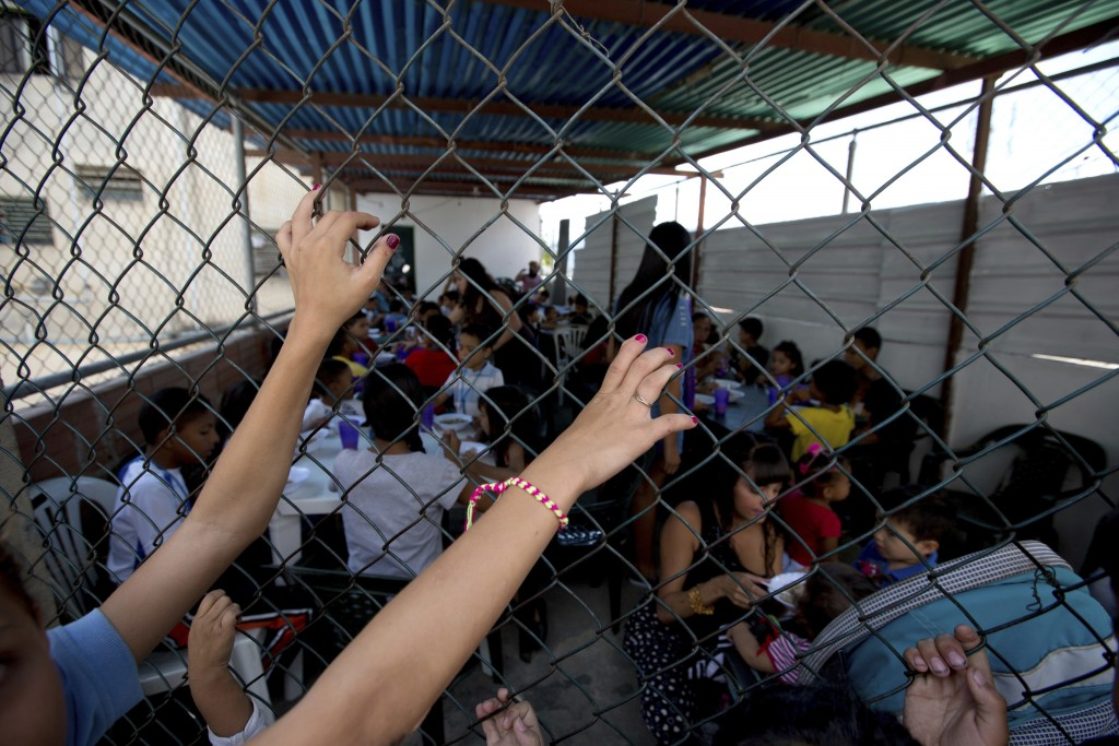 In this Dec. 12, 2017 photo, children wait their turn to enter a soup kitchen for a free meal, sponsored by the opposition in Caracas, Venezuela. The ...