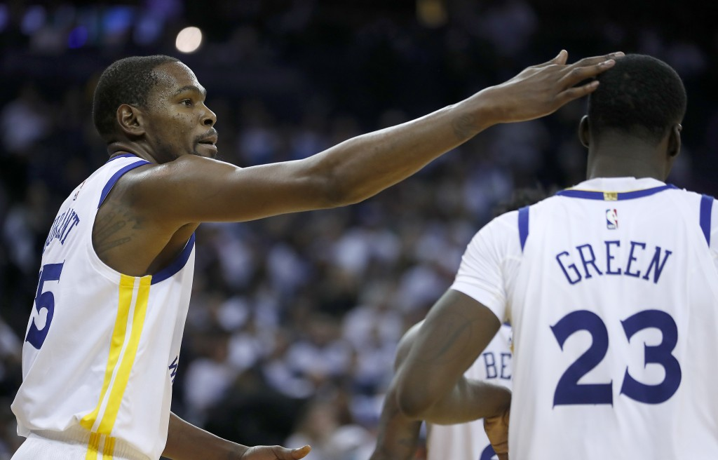 Golden State Warriors forward Kevin Durant (35) taps forward Draymond Green (23) on the head after scoring against the Cleveland Cavaliers during the ...