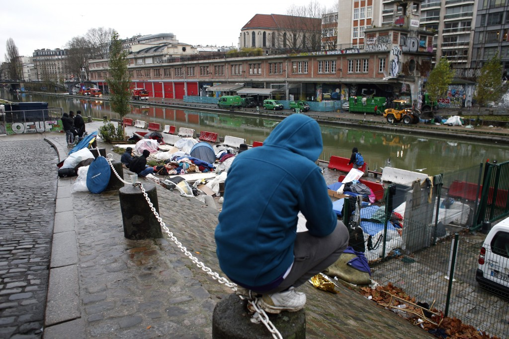 Migrants sit by a makeshift camp in Paris, Thursday, Dec. 21, 2017. The French government is scrambling to meet President Emmanuel Macron's deadline t...