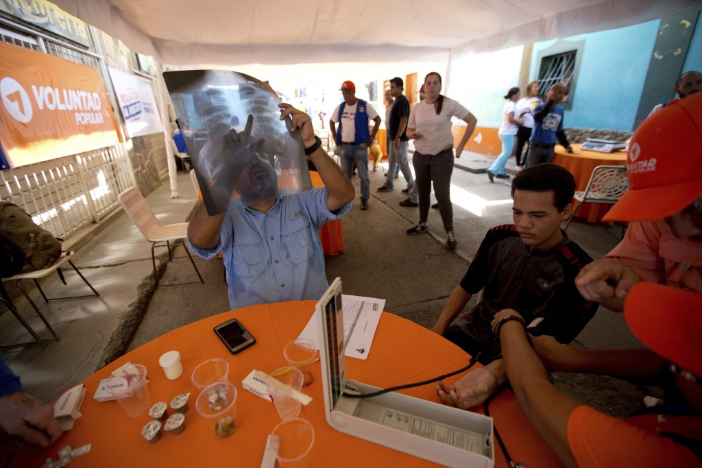 In this Dec. 9, 2017 photo, physician and opposition politician Winston Flores reads an ex-ray during a free medical campaign for the poor in La Guair...