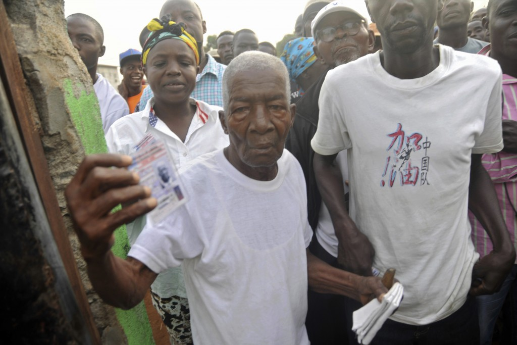 People wait to cast their votes during a Presidential runoff election in Monrovia, Liberia, Tuesday Dec. 26, 2017. Young Liberians went straight from ...