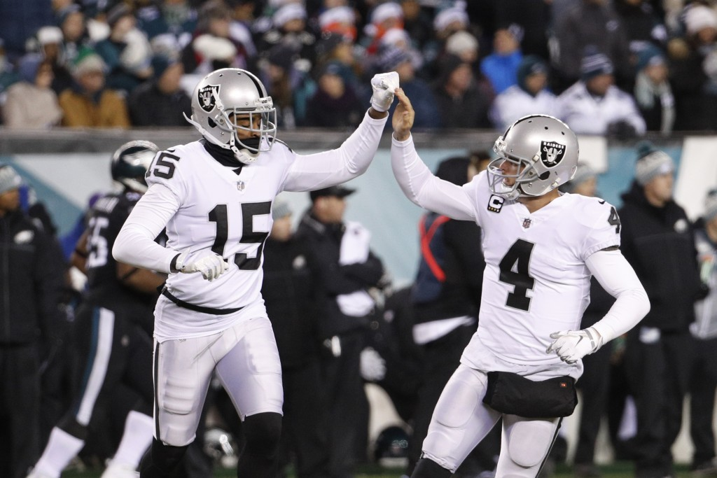 Oakland Raiders' Derek Carr, right, celebrates with Michael Crabtree after Carr passed for a touchdown during the first half of an NFL football game a...