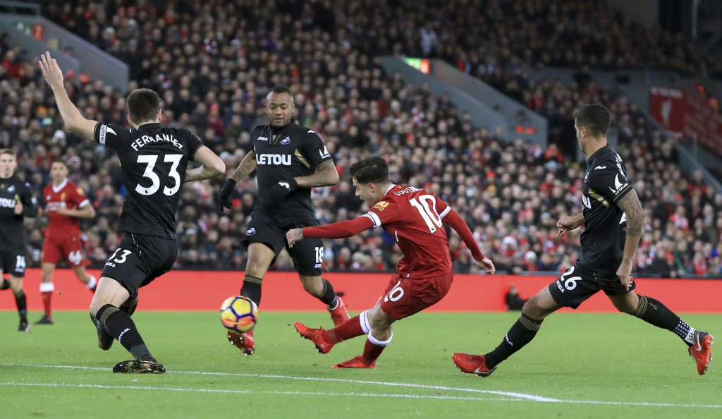 Liverpool's Philippe Coutinho scores his side's first goal of the game against Swansea City during the English Premier League soccer match at Anfield,...