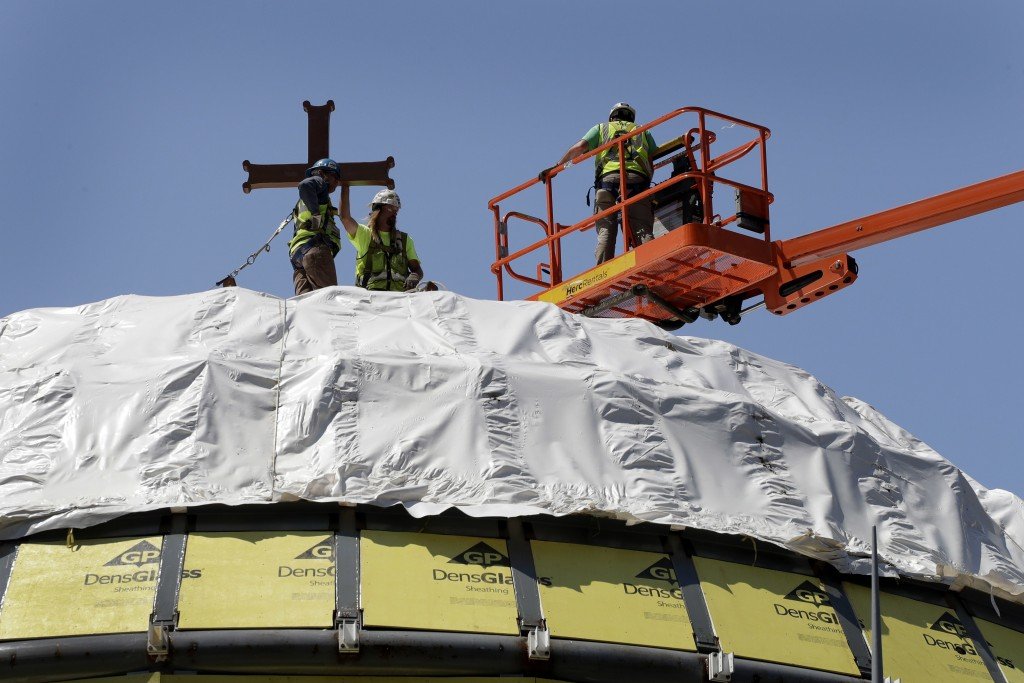 FILE- In this Aug. 10, 2017 file photo, construction workers adjust a temporary cross on the St. Nicholas National Shrine in New York. Work on the Gre...