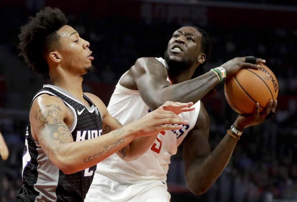 LA Clippers forward Montrezl Harrell, right, shoots around Sacramento Kings guard Malachi Richardson during the first half of an NBA basketball game i...