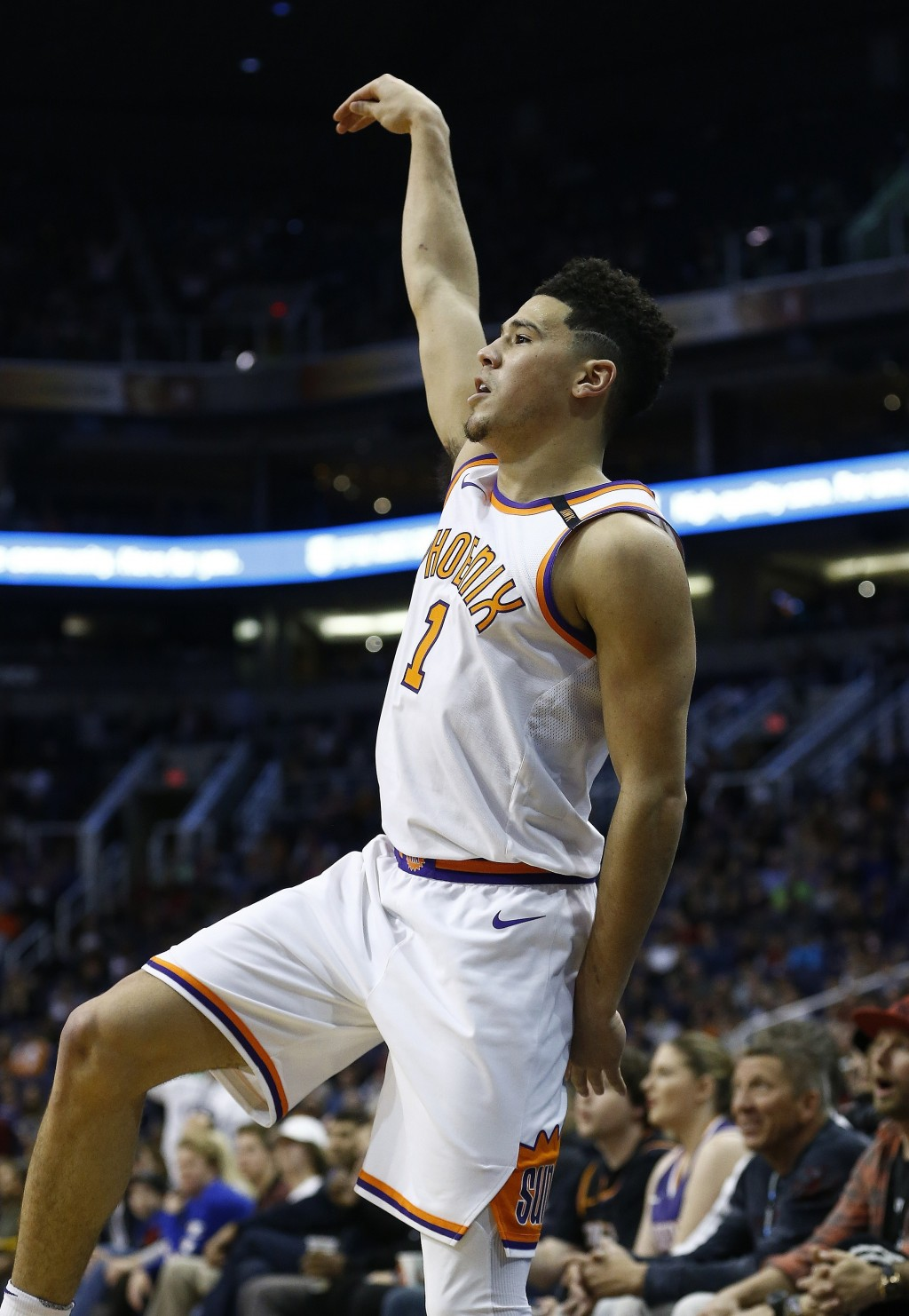 Phoenix Suns guard Devin Booker watches a 3-pointer go in during the first half of an NBA basketball game against the Memphis Grizzlies, Tuesday, Dec....