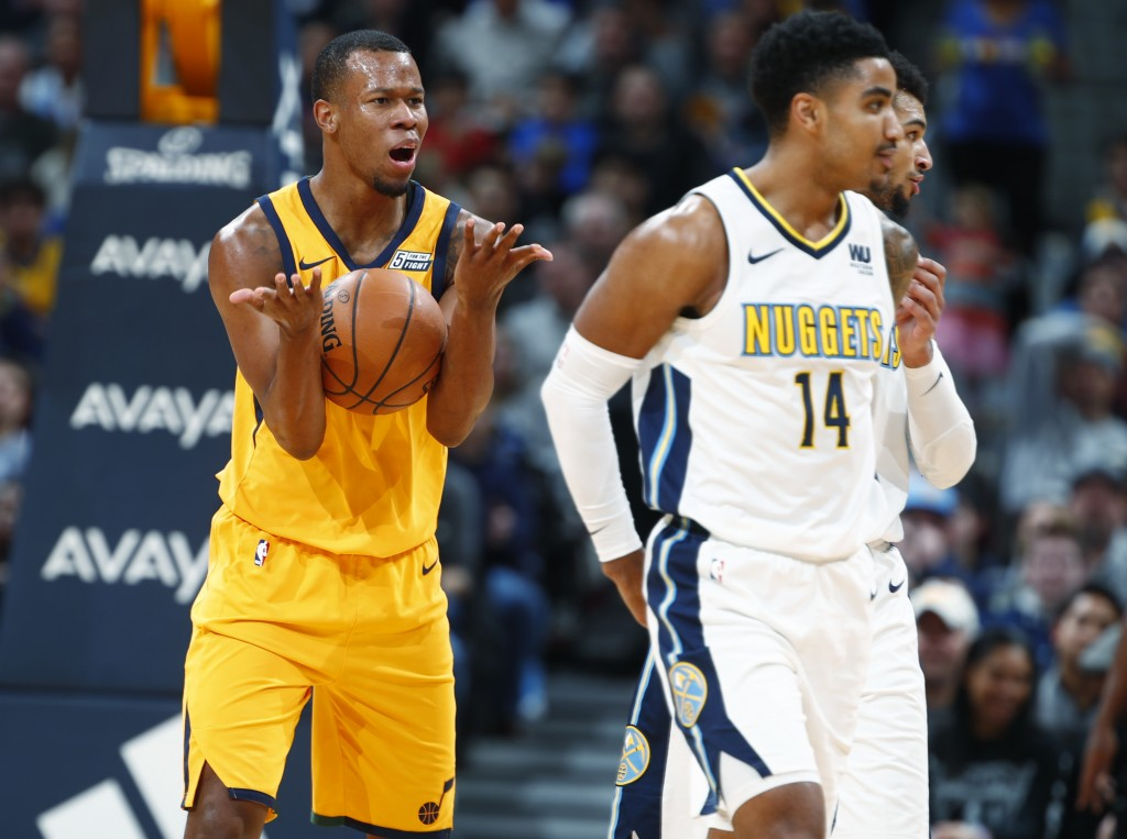 Utah Jazz guard Rodney Hood, back, argues after he was called for traveling as Denver Nuggets guard Gary Harris heads down the court in the first half...