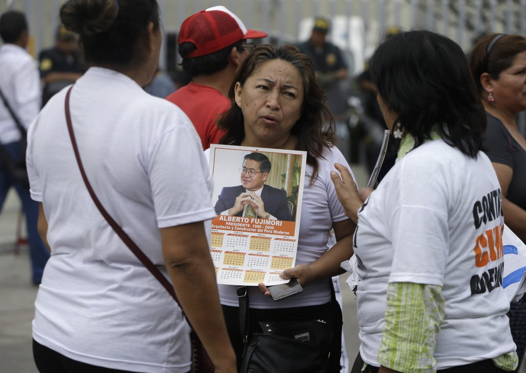 A small group of supporters of former President Alberto Fujimori talk outside the clinic where the jailed leader was hospitalized, in Lima, Peru, Tues...
