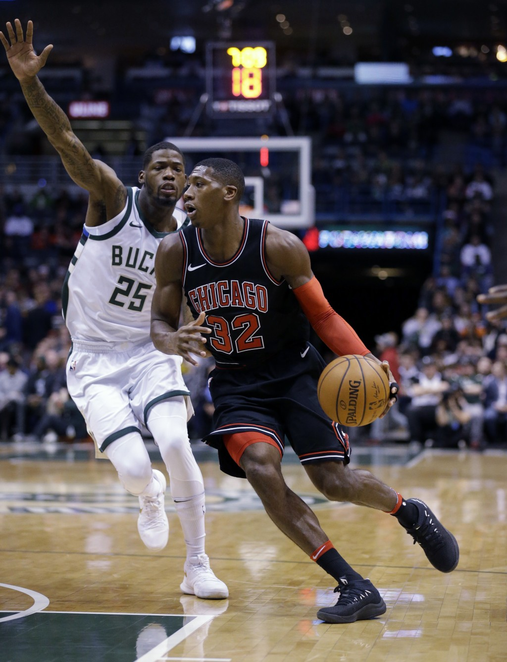 Chicago Bulls' Kris Dunn, right, drives past Milwaukee Bucks' DeAndre Liggins during the first half of an NBA basketball game, Tuesday, Dec. 26, 2017,...
