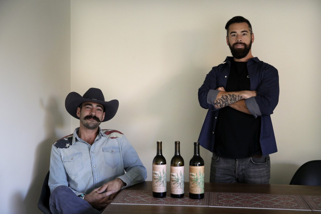 In this Friday, Dec. 22, 2017, photo, Alex Howe, right, and Chip Forsythe, co-founders of Rebel Coast, pause for photos with their cannabis-infused wi...