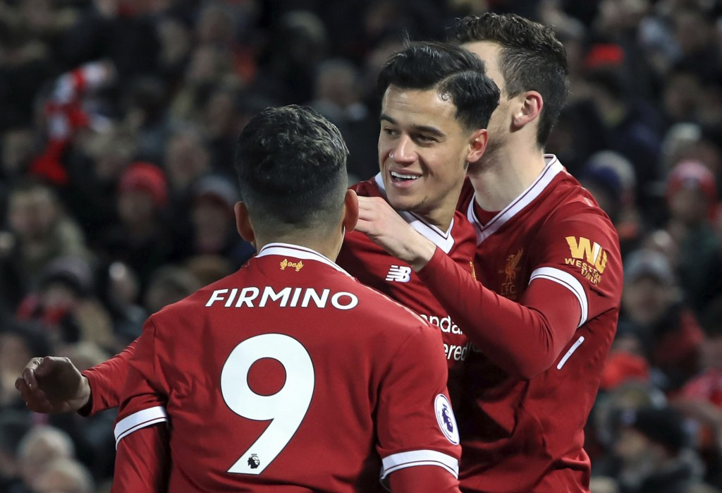 Liverpool's Philippe Coutinho, center, celebrates scoring his side's first goal of the game against Swansea City during the English Premier League soc...