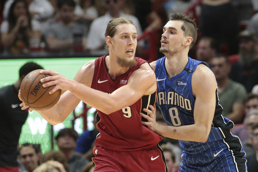 Orlando Magic guard Mario Hezonja (8) defends against Miami Heat center Kelly Olynyk (9) during the first half of an NBA basketball game, Tuesday, Dec...