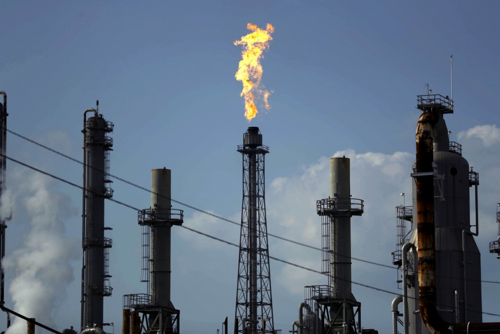 FILE - In this Thursday, Aug. 31, 2017, file photo, a flame burns at the Shell Deer Park oil refinery in Deer Park, Texas. The price of crude oil bare...