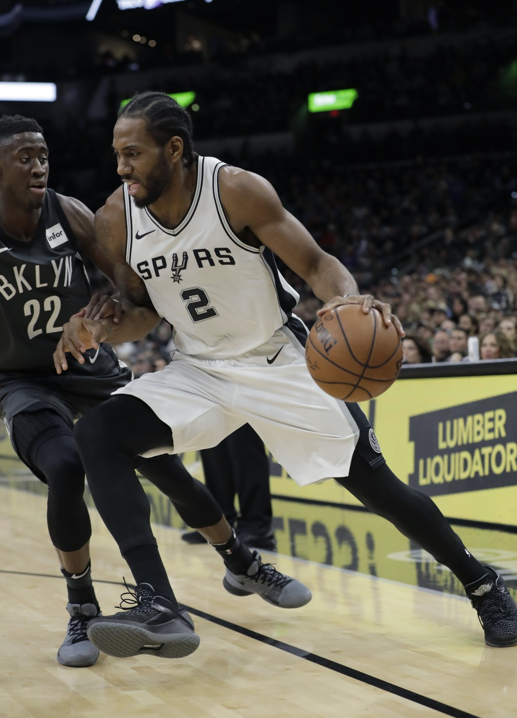 San Antonio Spurs forward Kawhi Leonard (2) drives around Brooklyn Nets guard Caris LeVert (22) during the first half of an NBA basketball game, Tuesd...