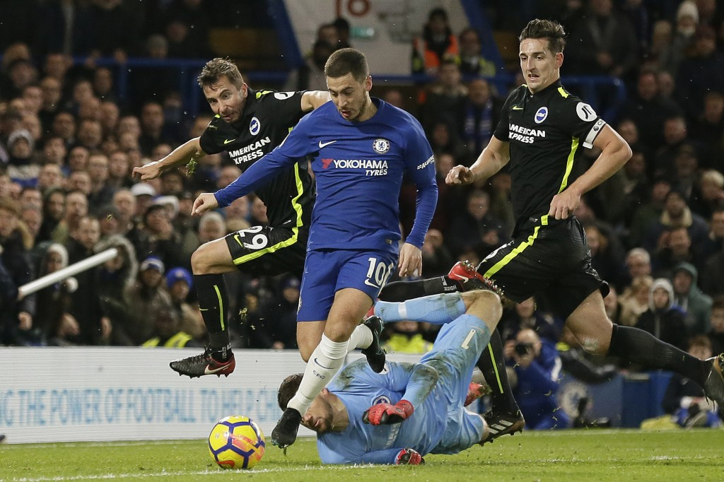 Chelsea's Eden Hazard, centre, beats Brighton's Markus Suttner, left, Matthew Ryan, bottom, and Lewis Dunk, right, during the English Premier League s...