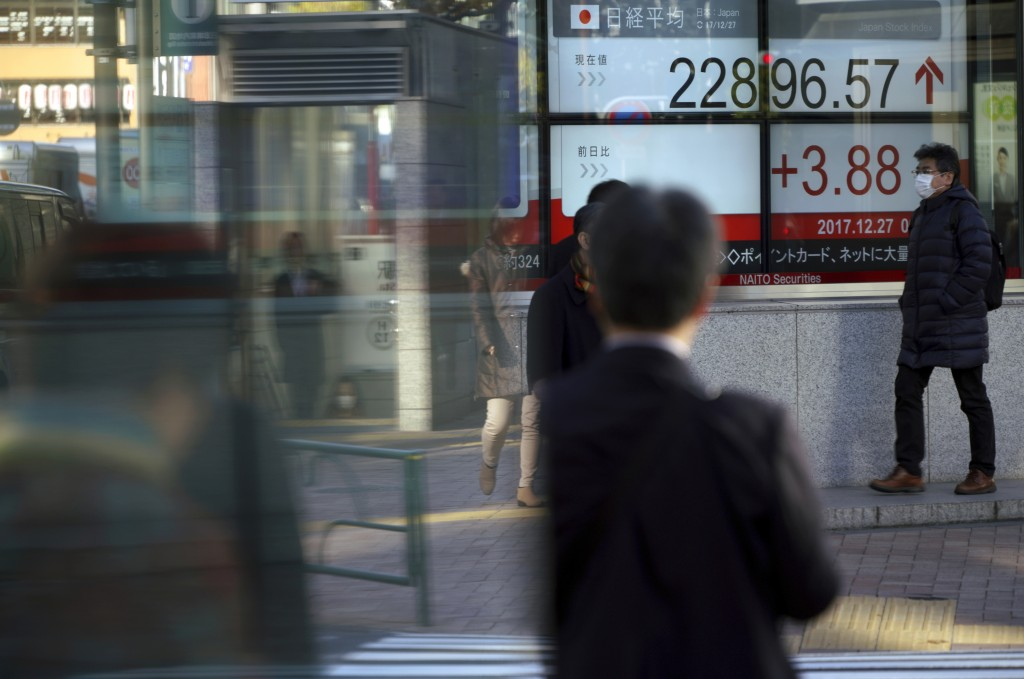 A man walks past an electronic stock board showing Japan's Nikkei 225 index at a securities firm in Tokyo Wednesday, Dec. 27, 2017. Asian indexes were...