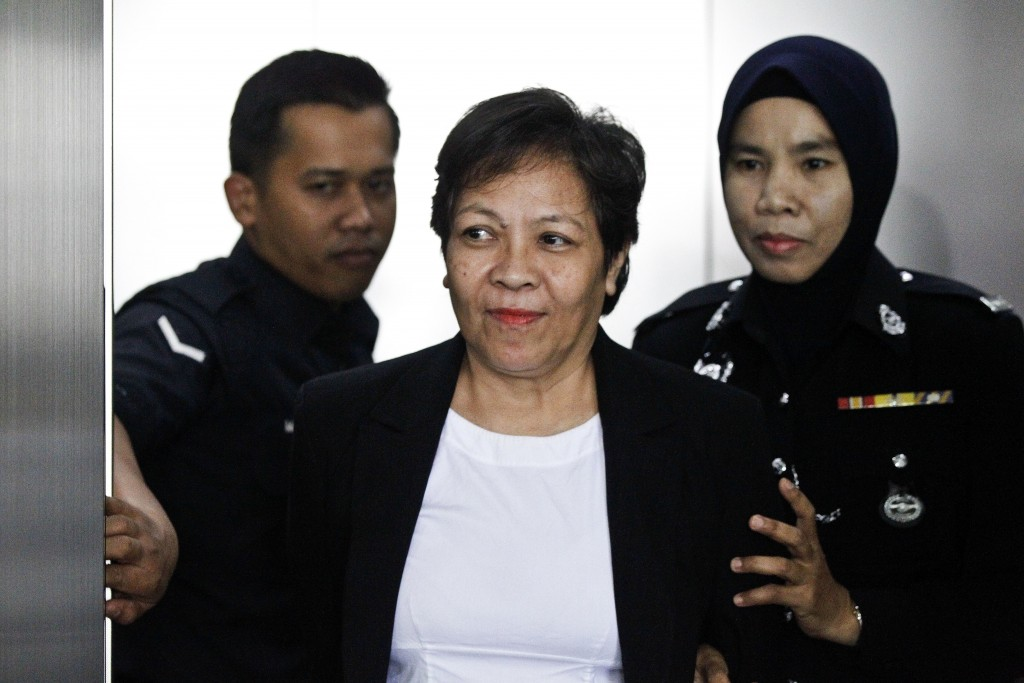 Australian Maria Elvira Pinto Exposto, center,  is escorted by a police officer during a court hearing at Shah Alam High Court in Shah Alam, Malaysia,