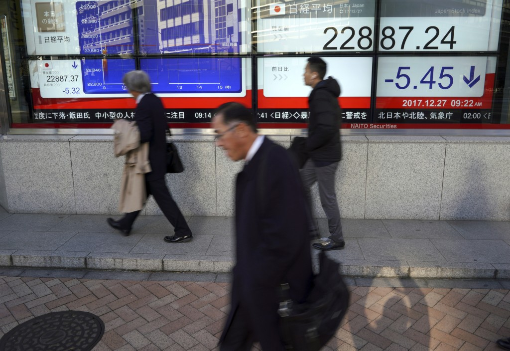 Men walk past an electronic stock board showing Japan's Nikkei 225 index at a securities firm in Tokyo Wednesday, Dec. 27, 2017.  Asian indexes were m...