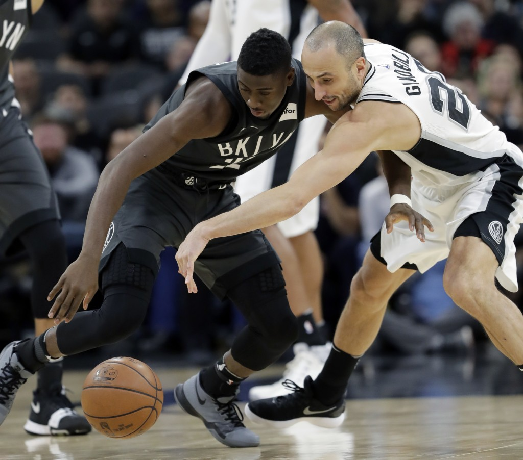 Brooklyn Nets guard Caris LeVert, left, and San Antonio Spurs guard Manu Ginobili, right. scramble for a loose ball during the first half of an NBA ba...
