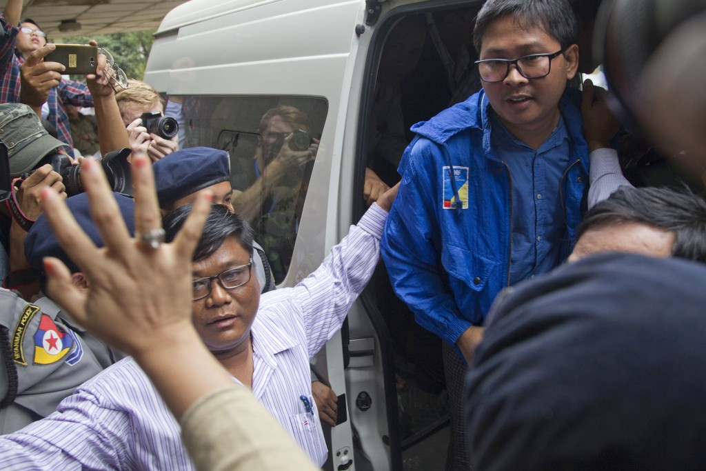 Reuters journalist Thet Oo Maung Maung, known as Wa Lone, exits a police van while his wife Pan Ei Mon waves upon his arrival at the township court fo...