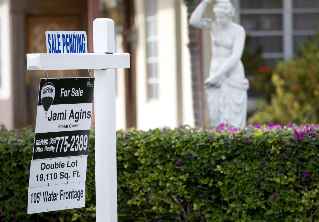 """FILE - In this Thursday, Jan. 8, 2015, file photo, a """"Sale Pending"""" placard is placed atop a realty sign outside a home for sale in Surfside, Fla. On ..."""