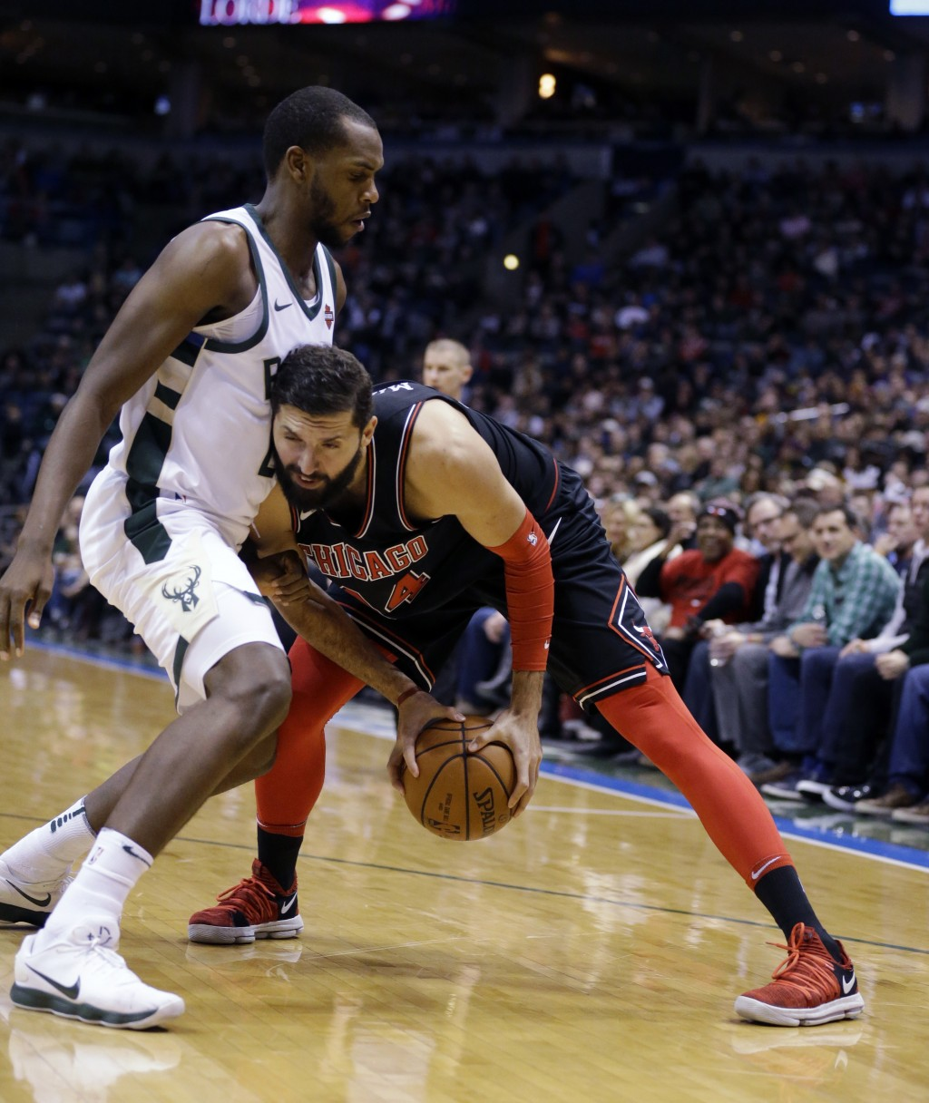 Chicago Bulls' Nikola Mirotic, right, looks to drive against Milwaukee Khris Middleton during the first half of an NBA basketball game Tuesday, Dec. 2...