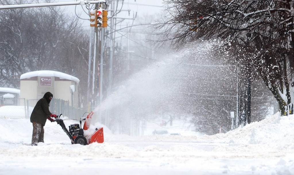 A man clears snow on Tuesday, Dec. 26, 2017, in Erie, Pa. The National Weather Service office in Cleveland says Monday's storm brought 34 inches of sn...