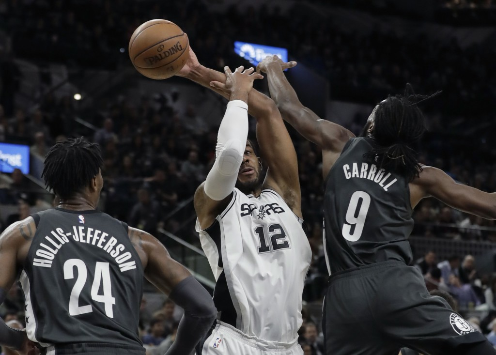 San Antonio Spurs forward LaMarcus Aldridge (12) is pressured by Brooklyn Nets forward DeMarre Carroll (9) as he tries to score during the first half ...