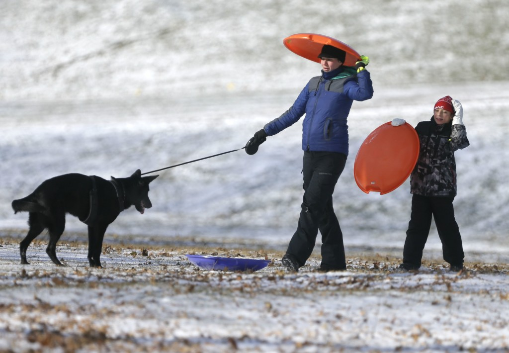 Elizabeth Gallagher and Ian Fullmer, 10, Glendale, enjoy sledding and time with their dog Cocoa along Lake Front Drive as single digit bitter cold tem...