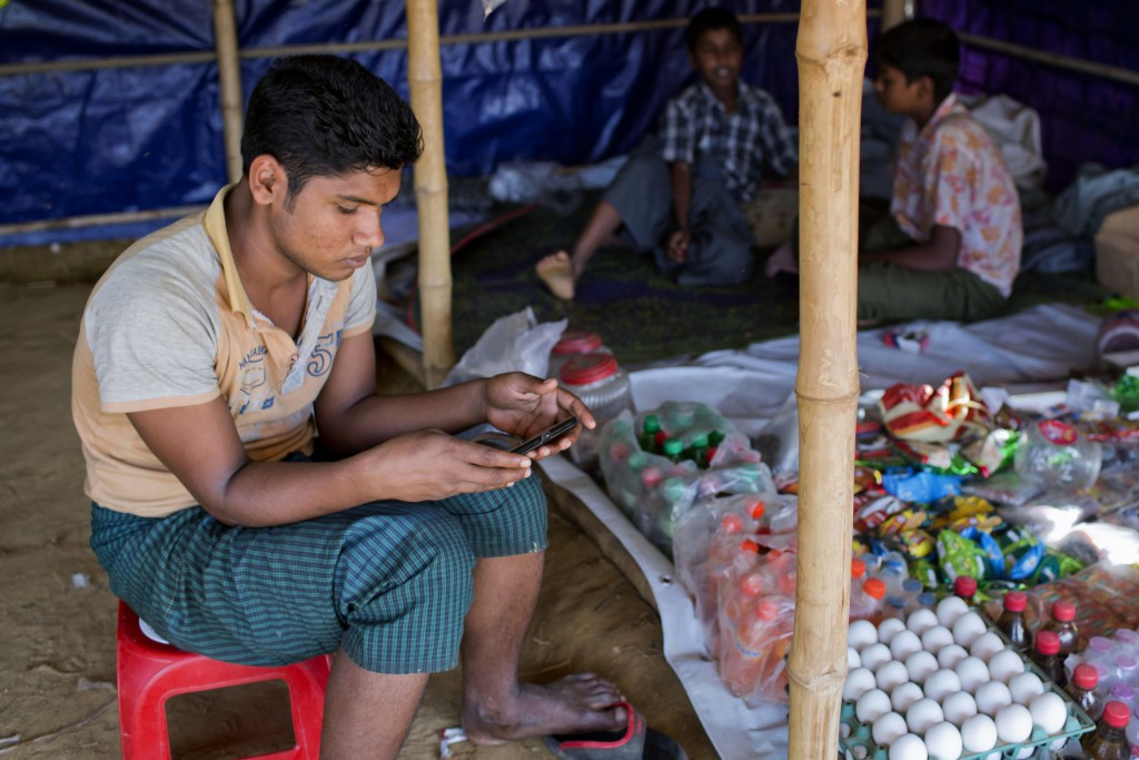 In this Dec. 23, 2017 photo, an unidentified Rohingya refugee watches a video, which he has shot in Myanmar before crossing over into Bangladesh, at K...