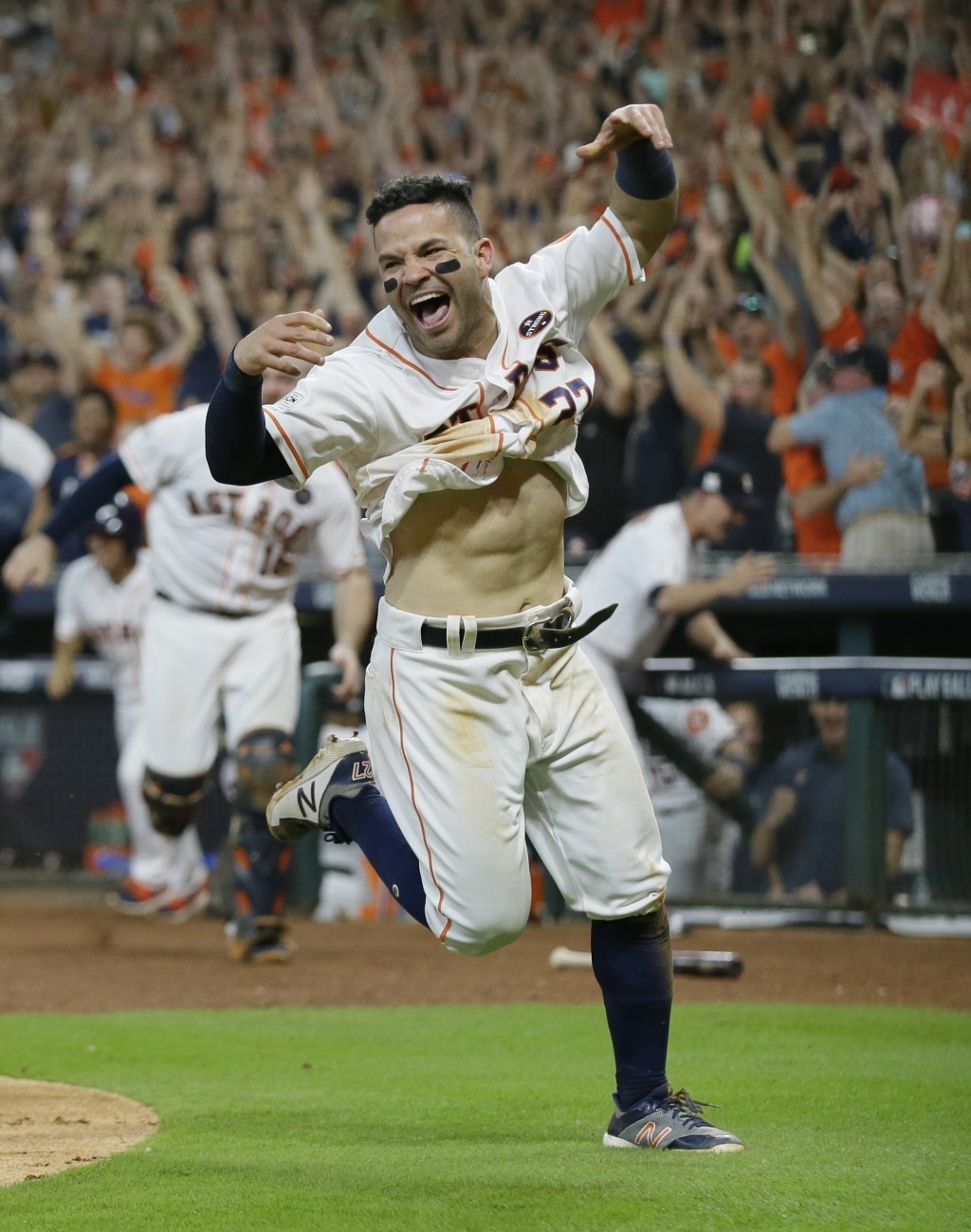 FILE - In this Oct. 14, 2017, file photo, Houston Astros' Jose Altuve reacts after scoring the game-winning run during the ninth inning of Game 2 of b...