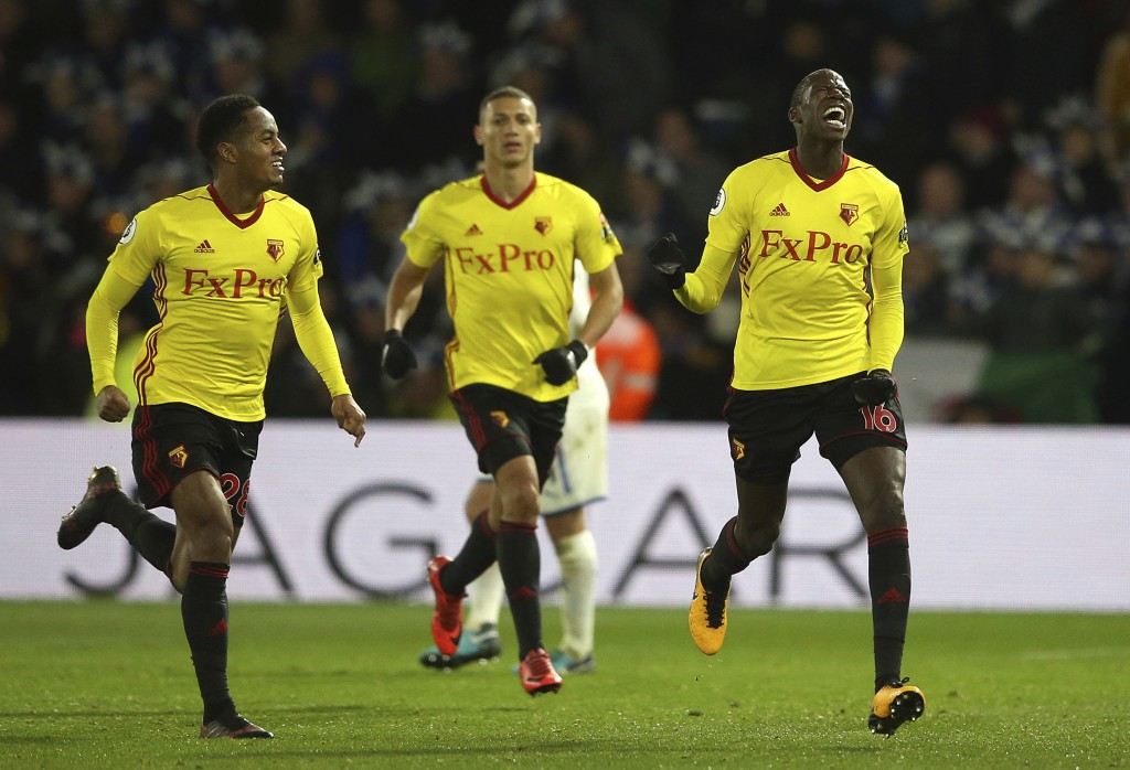 Watford's Abdoulaye Doucoure, right, celebrates with teammates after his effort was turned in by Leicester City goalkeeper Kasper Schmeichel for their...