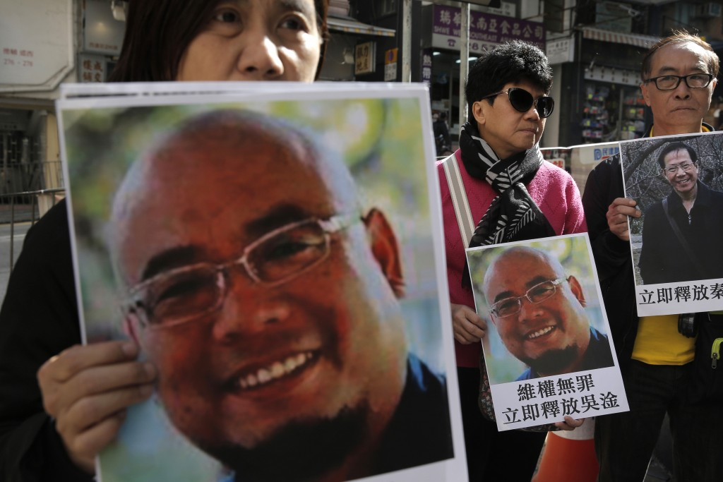 In this Dec. 27, 2017, file photo, pro-democracy activists hold pictures of Chinese activist Wu Gan near the Chinese central government's liaison offi...
