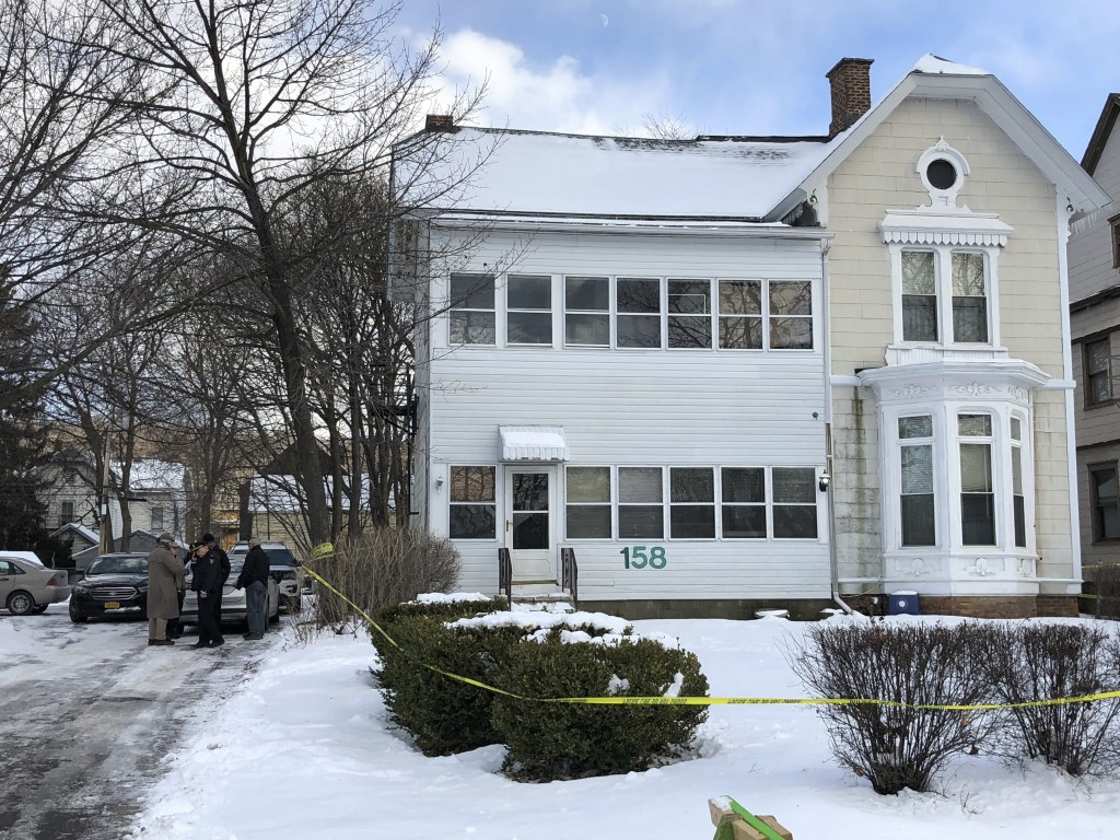 Police secure the perimeter of a home in Troy, N.Y., Tuesday, Dec. 26, 2017, after four bodies were discovered in a basement apartment. Troy police sa...