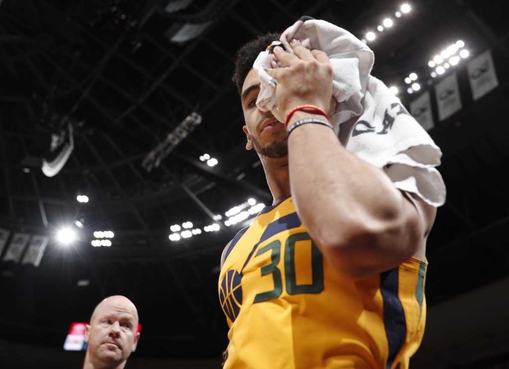 Utah Jazz guard Naz Mitrou-Long holds a towel to his forehead as he bleeds while heading to the locker room after injuring his head in a fall against ...