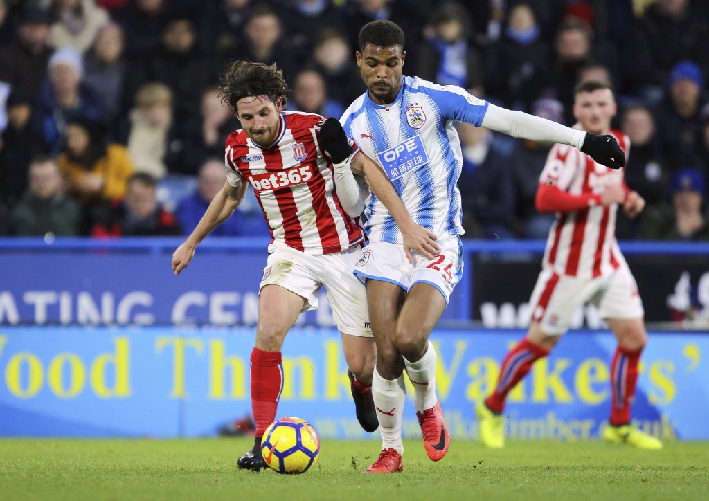 Stoke City's Joe Allen, left, and Huddersfield Town's Steve Mounie battle for the ball during their English Premier League soccer match at the John Sm...