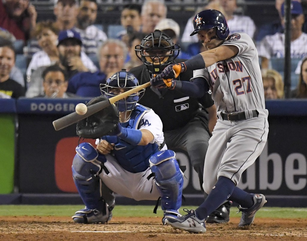 FILE - In this Oct. 25, 2017, file photo, Houston Astros' Jose Altuve hits a home run against the Los Angeles Dodgers during the 10th inning of Game 2...