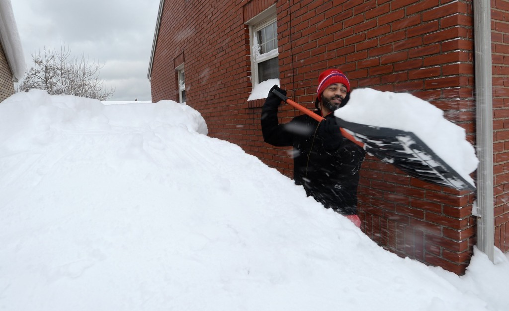 Patrick Harden clears snow from the roof of his car on Tuesday, Dec. 26, 2017, in Erie, Pa. The National Weather Service office in Cleveland says Mond...