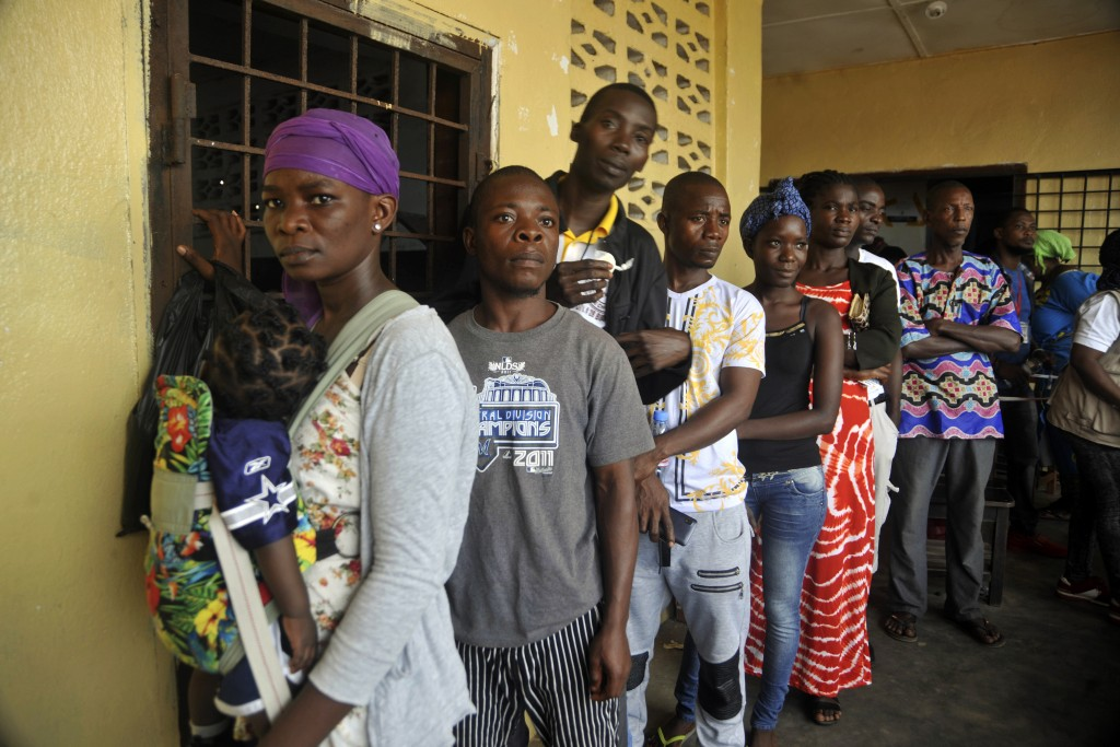 People wait to cast their votes during a Presidential runoff election in Monrovia, Liberia, Tuesday Dec. 26, 2017, Young Liberians went straight from ...