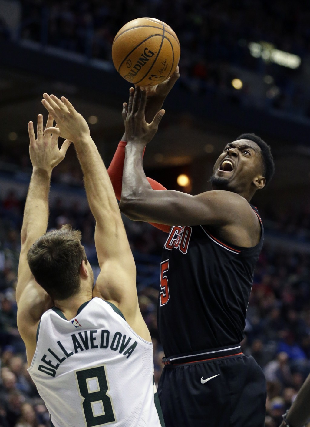 Chicago Bulls' Bobby Portis, right, puts up a shot against Milwaukee Bucks' Matthew Dellavedova during the first half of an NBA basketball game, Tuesd...