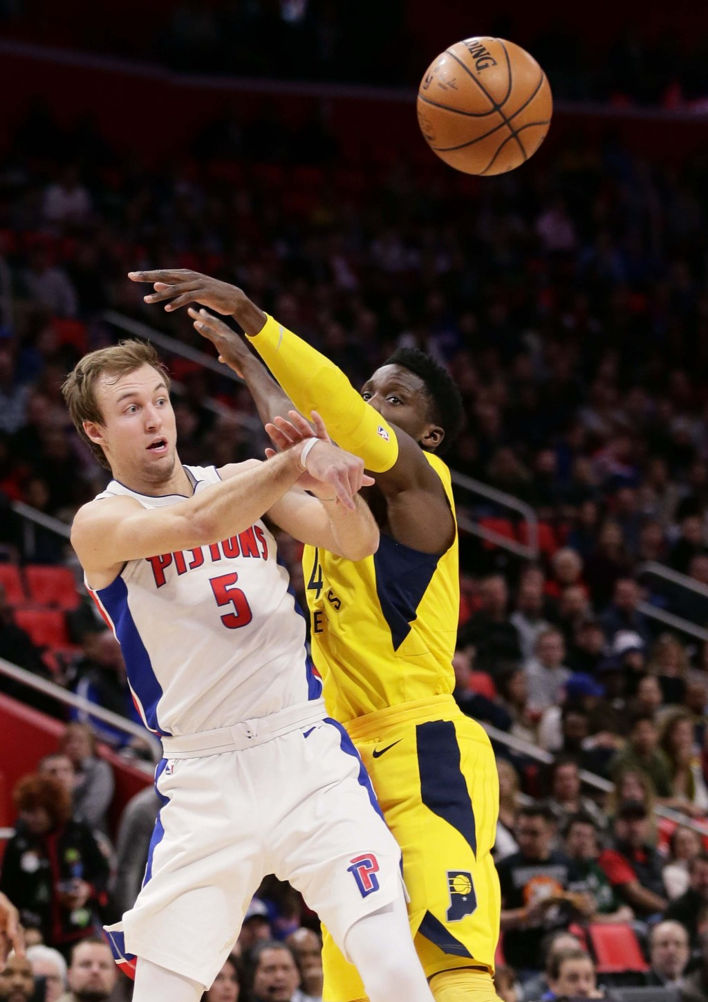 Detroit Pistons guard Luke Kennard (5) passes the ball against Indiana Pacers guard Victor Oladipo during the first half of an NBA basketball game, Tu...