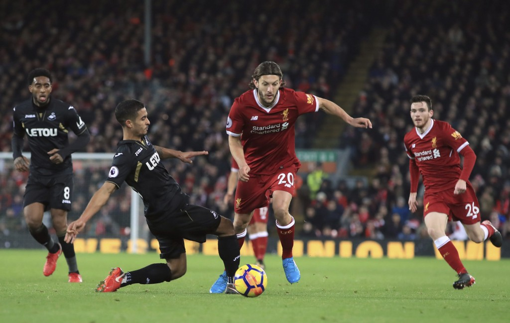 Liverpool's Adam Lallana and Swansea City's Kyle Naughton, left, battle for the ball during the English Premier League soccer match at Anfield, Liverp...