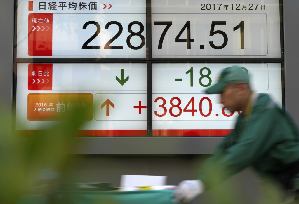A delivery man pushes a cart past an electronic stock board showing Japan's Nikkei 225 index at a securities firm in Tokyo Wednesday, Dec. 27, 2017. A...