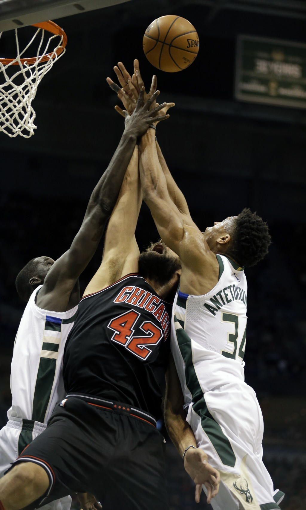 Chicago Bulls' Robin Lopez (42) reaches for a rebound between Milwaukee Bucks' Thon Maker, left, and Giannis Antetokounmpo during the first half of an...